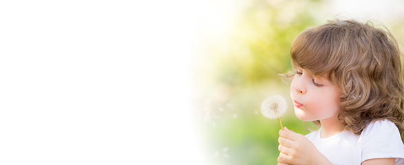 Little girl blowing out a dandelion